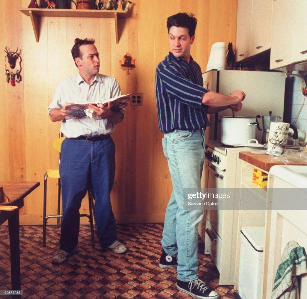 Humorist/writer David Sedaris reading cookbook to his partner, painter Hugh Hamrick, who is cooking at stove in their kitchen.