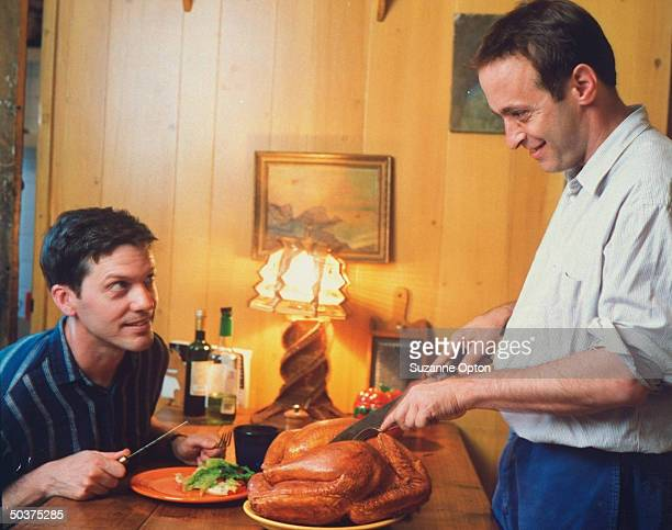 Humorist/writer David Sedaris slyly pretending to carve a rubber turkey as his amused partner painter Hugh Hamrick looks on hungrily at their apt