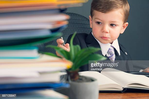 Humorous business manager concept. Young child in a suit working