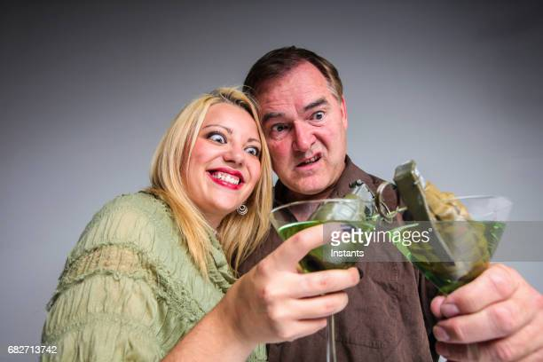 Humorous concept of an explosive relationship, may it be a couple or business, where a man and a woman are holding martinis, with each a grenade in their glass.