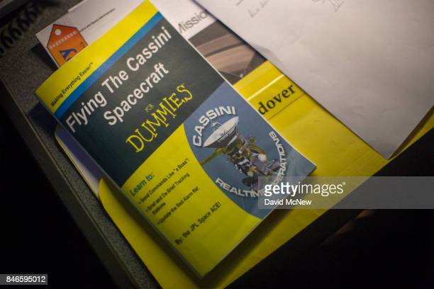A humorous cover on a manual is seen on the Cassini Mission Ace desk in JPL Mission Control at Jet Propulsion Laboratory as NASA's Cassini spacecraft...