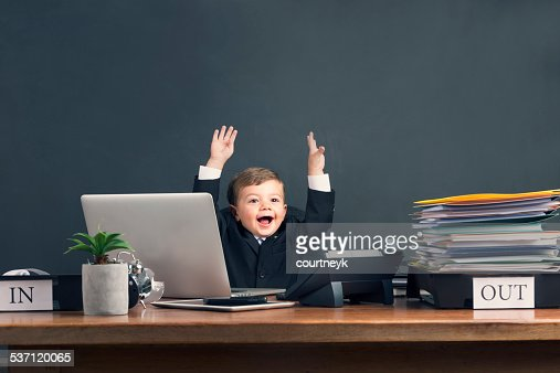 Humorous image of young boy working on a laptop computer