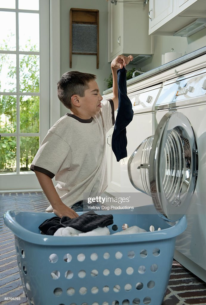Humorous Picture of Boy doing Laundry Chores : Stock Photo