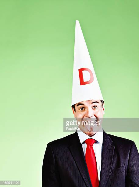 Humorous portrait of businessman in dunce cap sticking out tongue