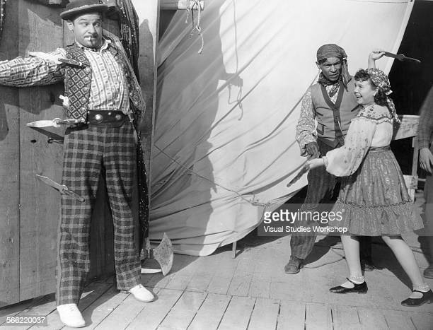 A humorous shot of a young Jane Withers an American actress pretending to throw knives at Borrah Minevitch a noted harmonica player and actor early...