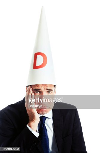 Humorous shot of embarrassed ashamed businessman in dunce cap
