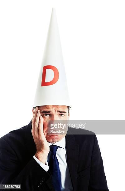 Humorous shot of embarrassed ashamed businessman in dunce cap