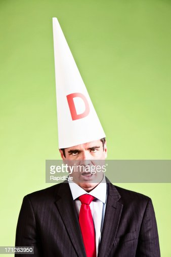 Humorous study of businessman looking dumb in dunce cap