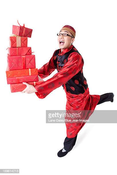 Humorous young man in Tang suit holding gift boxes
