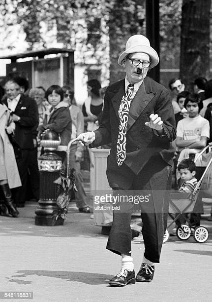 humour people visitors on a sqare have fun with a costumed comedian aged 60 to 70 years Great Britain England London