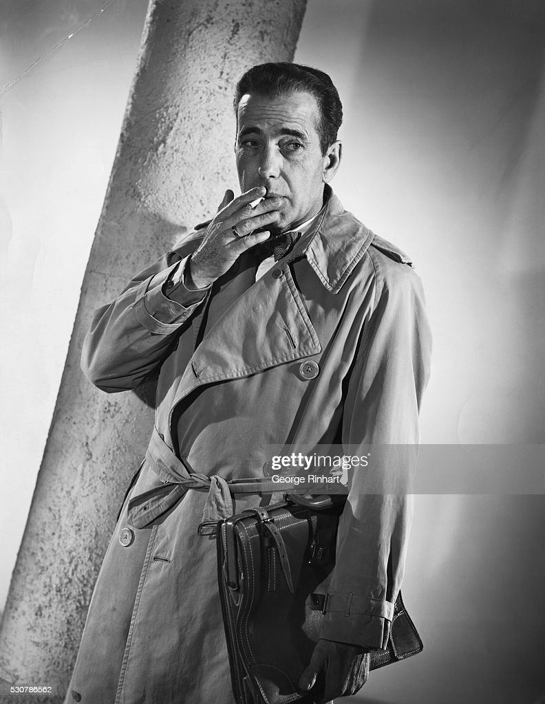 Humphrey Bogart in promotional photo for the film 'Sirocco' with Bogey in a classic pose with cigarette in mouth and wearing trench coat 1951