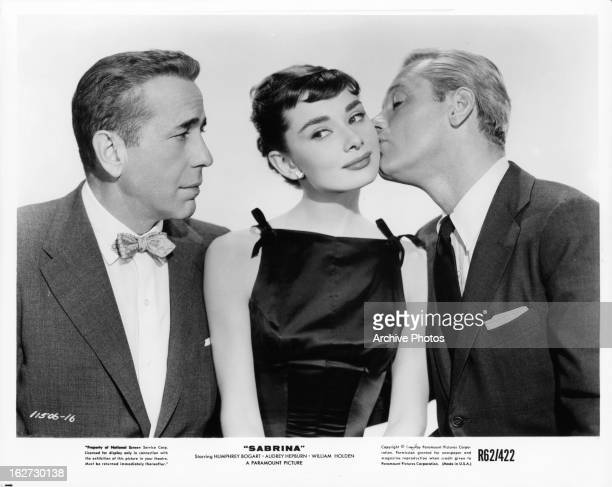 Humphrey Bogart is disheartened to see Audrey Hepburn being kissed by William Holden in publicity portrait for the film 'Sabrina' 1954