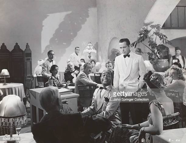 Humphrey Bogart listens to Dooley Wilson play piano and sing 'As Time Goes By' at Rick's in this crowded nightclub scene from 'Casablanca'