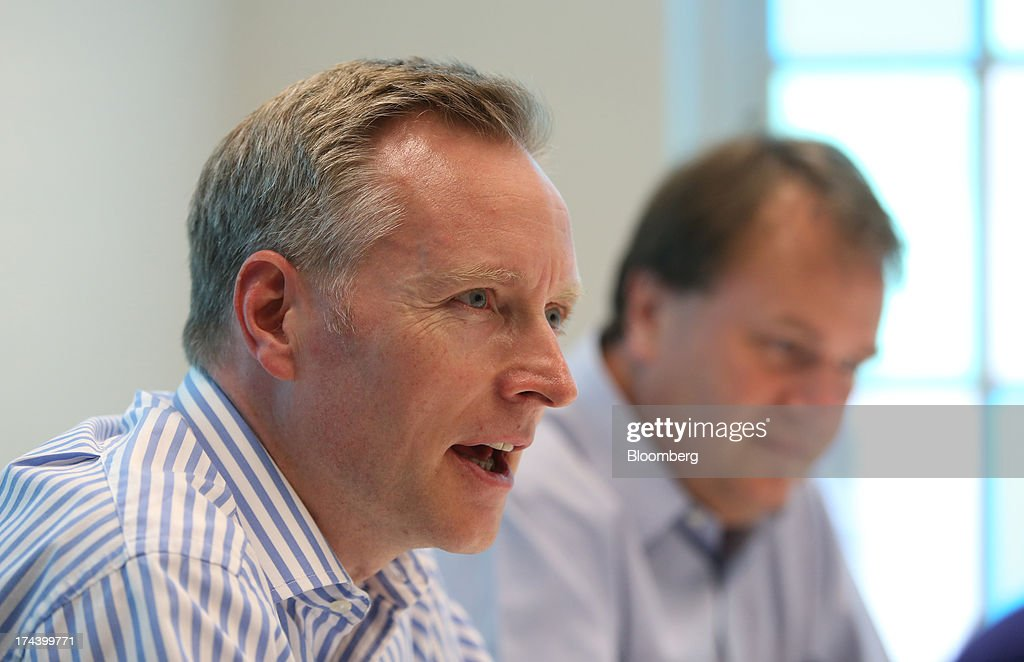 Humphrey Singer, group finance director of Dixons Retail Plc, left, speaks as Sebastian James, chief executive officer of Dixons Retail Plc, listens during an interview in London, U.K. on Thursday, July 25, 2013. The owner of the PC World and Currys chains is training staff to improve customer relations and is selling higher-margin services to overcome cheaper online competitors. Photographer: Chris Ratcliffe/Bloomberg via Getty Images