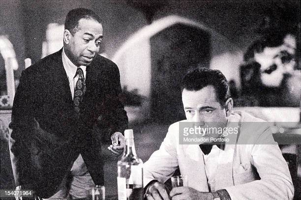 Humprey Borgat sit in a night club with Dooley Wilson in a scene of Casablanca 1942