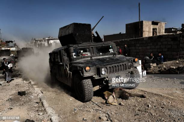 Humvee passes over the body of a jihadist in west Mosul on March 10 2017 as Iraqi forces advance in the city in the ongoing battle to seize it from...