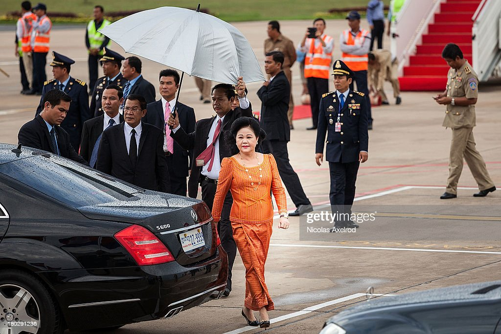 PM <a gi-track='captionPersonalityLinkClicked' href=/galleries/search?phrase=Hun+Sen&family=editorial&specificpeople=224084 ng-click='$event.stopPropagation()'>Hun Sen</a> and his wife Bun Rany leave the airport after greeting King Norodom Sihamoni and Queen Mother Norodom Monineath at the Phnom Penh airport on September 11, 2013 in Phnom Penh, Cambodia. King Norodom Sihamoni returns to Cambodia amid election controversy and has been asked by the opposition leader to intervene in the election dispute. The King had been in China where it is said he was receiving a medical check up.