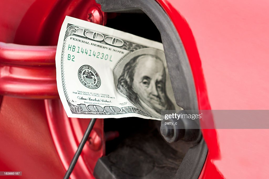 A hundred dollar bill stuffed into a cars gas tank : Stock Photo