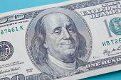 US hundred dollar bill with smiling and winking Benjamin Franklin