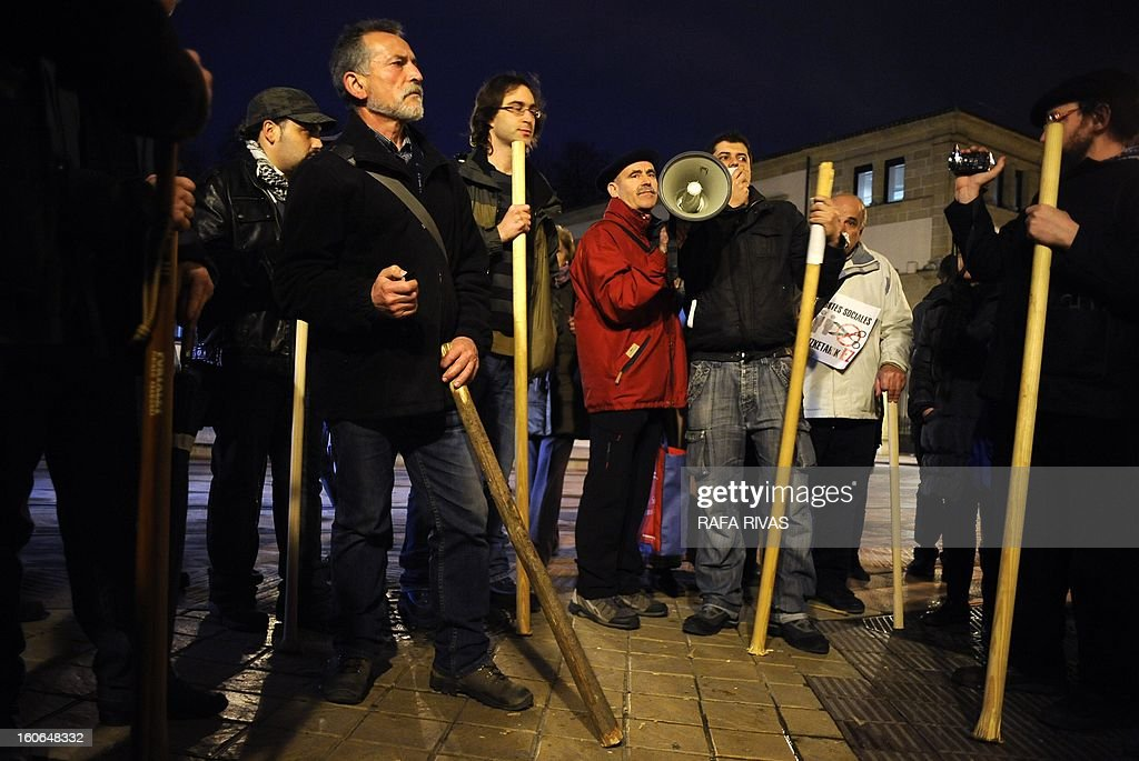 Hundreds of demonstrators called by Antigona civil disobedience group gather in front of the Basque regional parliament to protest against antisocial political decisions and government corruption hitting the ground with staffs, on the eve of Saint Agueda day, in the Northern Spanish Basque city of Vitoria, on February 4, 2013. Traditionally people walk the streets hitting the ground with staffs during Saint Agueda day to wake the earth before spring.