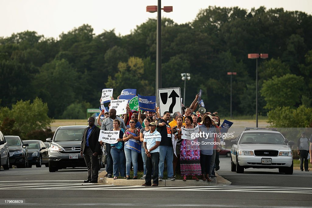 Hundreds of demonstrators march and block traffic in a major intersection outside a Walmart store during rush hour September 5, 2013 in Hyattsville, Maryland. Six women were arrested during the demonstration where about 225 people gathered outside the Walmart store to protest the retail giant's labor practices. A showdown continues between Walmart and the neighboring District of Columbia, where Mayor Vincent Gray could sign a bill that would make large retailers to pay their employees a 50 percent premium over the city's minimum wage.