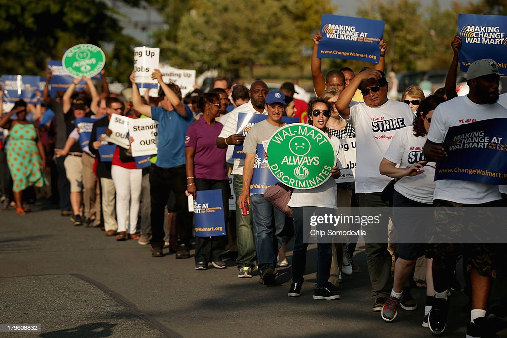 Hundreds of demonstrators march before blocking traffic in a major intersection outside a Walmart store during rush hour September 5, 2013 in Hyattsville, Maryland. Six women were arrested during the demonstration where about 225 people gathered outside the Walmart store to protest the retail giant's labor practices. A showdown continues between Walmart and the neighboring District of Columbia, where Mayor Vincent Gray could sign a bill that would make large retailers to pay their employees a 50 percent premium over the city's minimum wage.