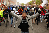 Hundreds of demonstrators march toward the Baltimore Police Western District station during a protest against police brutality and the death of...