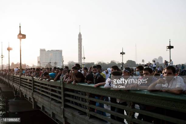Hundreds of Egyptians watch the progress of clashes between protesters and riot police from the famous Kasr al Nil bridge near the United States...