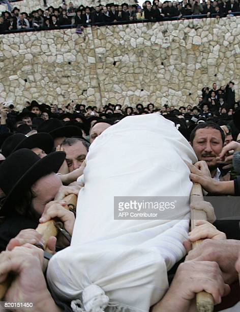 Hundreds of faithful look on as the body of Rabbi Yitzhak Kaduri is taken for burial at the Givat Shaul cemetery in Jerusalem 29 January 2006...