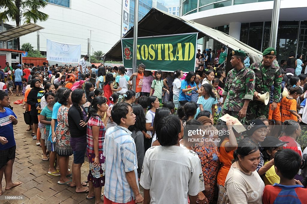Hundreds of flood victims queue for relief goods at a distribution center while soldiers keep order in Jakarta on January 24, 2013. Indonesia's National Disaster Mitigation Agency (BNPB) said more than 30,000 people were displaced while 20 people died during the widespread flooding that hit Jakarta as the weather bureau forecast more rains in the coming days.