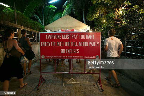 Hundreds of full moon partiers head onto the Haad Rin beach paying 100 Thai bhat on August 21 2013 in Koh Phangan Thailand Thousands of people from...