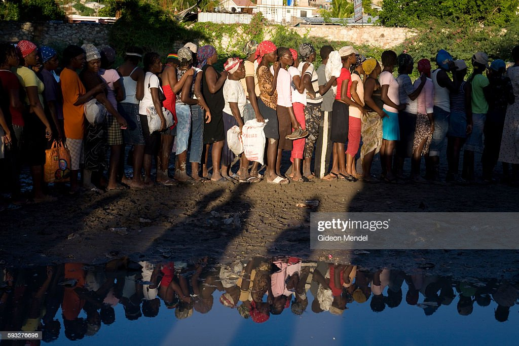 Hundreds of hungry people queue for food relief in the flooded city of Gonaives some of them reflected in the remaining floodwater Two weeks earlier...