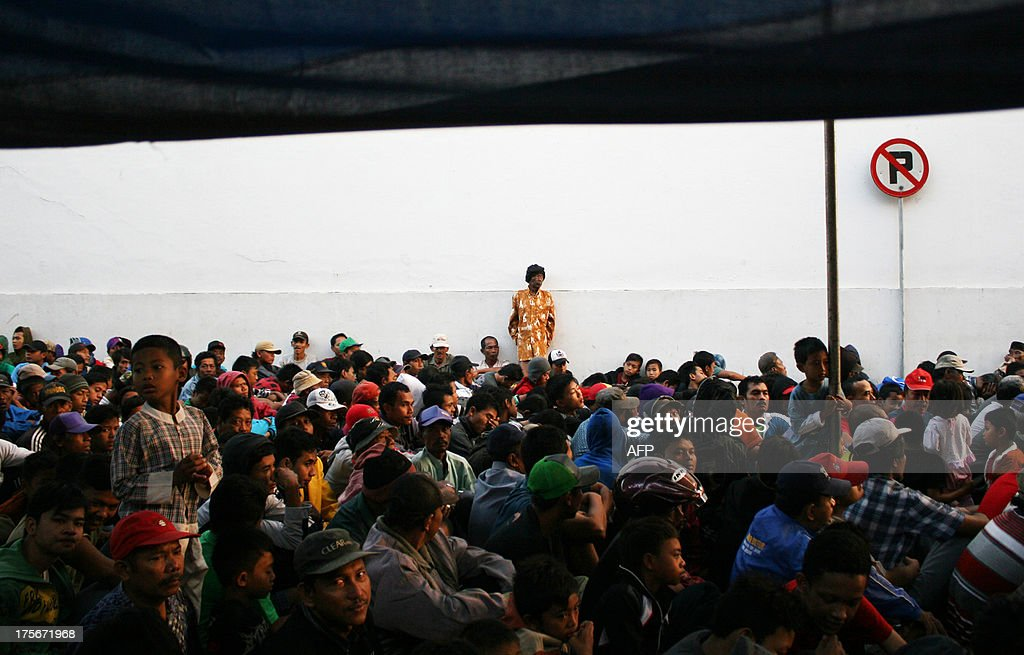 Hundreds of Indonesians wait to receive 'zakat', or alms, given to poor people during Ramadan at a tabacco factory of Gudang Garam, Indonesia's biggest clove cigarette manufacturer, in Kediri in East Java province on August 6, 2013. Each person received 10,000 (1 USD) or up to 20,000 rupiah (2 USD) cash from company in a tradition of giving charity to the poor during Islam's holy month of Ramadan.