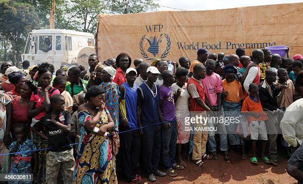 Hundreds of internally displaced persons wait near the airport in Bangui for food handouts from the UN World Food Programme on December 13 2013 The...