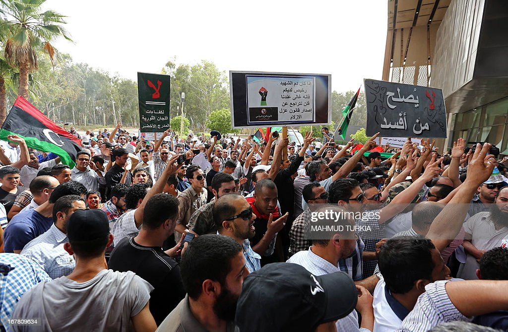 Hundreds of Libyan protesters shout slogans as they demonstrate outside the Libyan General National Congress in support of the 'Political Isolation Law' which calls for the expulsion of former regime employees from top government and political posts on April 30, 2013 in Tripoli. Armed men demanding the expulsion of former officials of the regime of ousted Libyan leader Moamer Kadhafi surrounded the justice ministry in the capital, widening a campaign that began on the weekend with a siege on the foreign ministry, an official said.