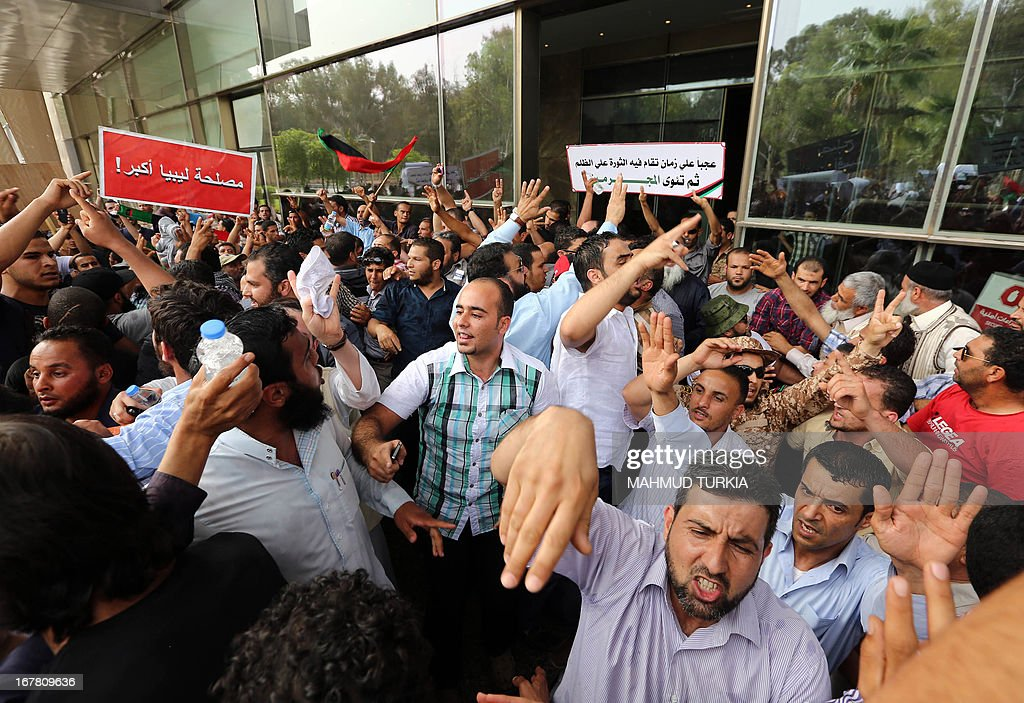 Hundreds of Libyan protesters shout slogans as they demonstrate outside the Libyan General National Congress in support of the 'Political Isolation Law' which calls for the expulsion of former regime employees from top government and political posts on April 30, 2013 in Tripoli. Armed men demanding the expulsion of former officials of the regime of ousted Libyan leader Moamer Kadhafi surrounded the justice ministry in the capital, widening a campaign that began on the weekend with a siege on the foreign ministry, an official said. AFP PHOTO/MAHMUD TURKIA