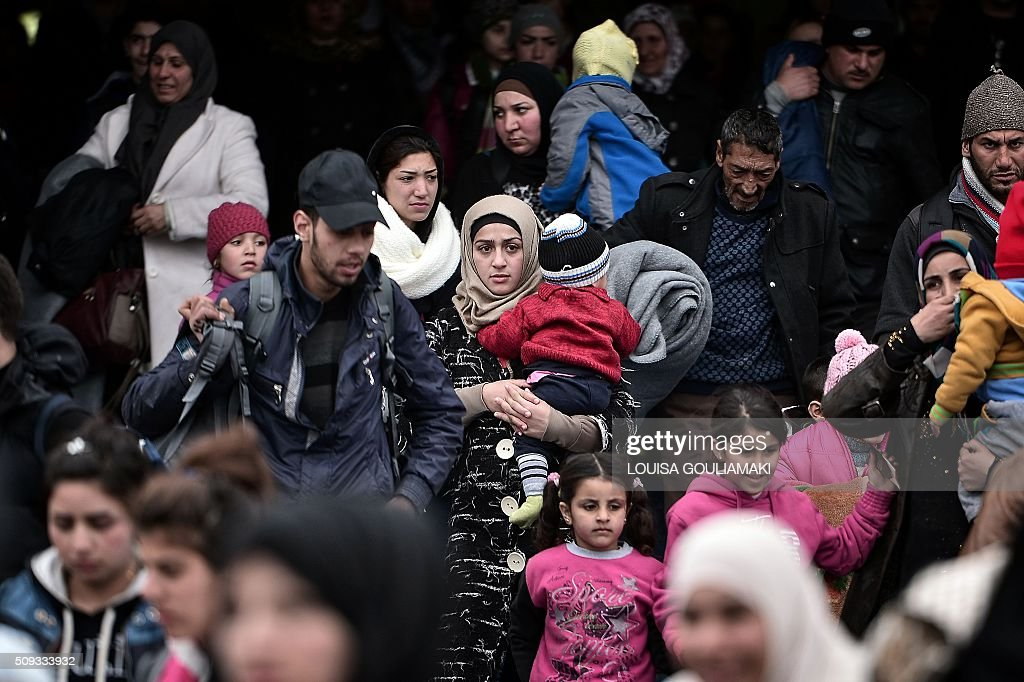Hundreds of migrants and refugees disembark from a ferry at the port of Piraeus on February 10, 2016. EU migration commissioner Dimitris Avramopoulos said on February 10, 2016 he has written letters to member states with a 'clear and strong message' to accelerate the relocation of refugees from overstretched Greece and Italy. Streams of people fleeing conflict or poverty continue to make the often perilous journey from Turkey across the Mediterranean and through the Balkans, despite cold winter weather, in the hope of starting new lives in more prosperous European countries. / AFP / LOUISA GOULIAMAKI