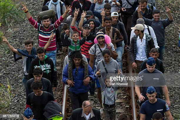 Hundreds of migrants guarded by police walk several miles along rail tracks towards the town of Szeged after breaking away from a collection point...