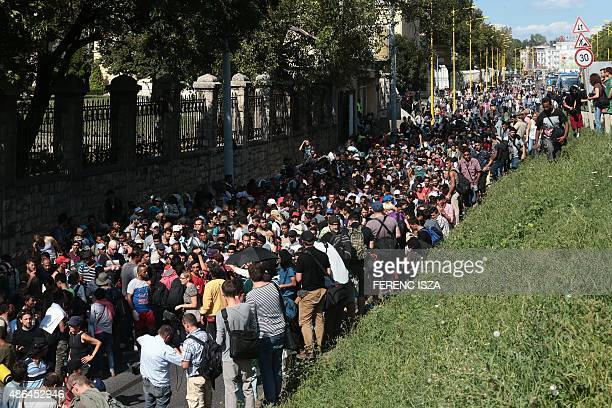Hundreds of migrants walk after leaving the transit zone of the Budapest main train station on September 4 2015 intenting on walking to the Austrian...