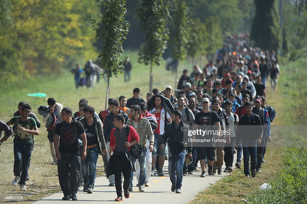 Hundreds of migrants who arrived by train at Hegyeshalom on the Hungarian and Austrian border walk the four kilometres into Austria on September 23...