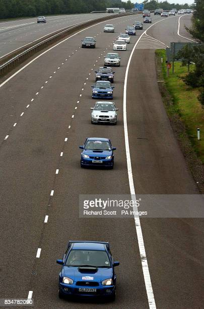 Hundreds of motor racing fans form a convoy of Subarus on the M74 motorway after leaving rally driver Colin McRae's home town of Lanark Scotland to...