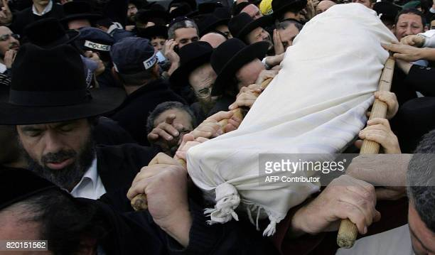 Hundreds of mourners gather as the body of Rabbi Yitzhak Kaduri is taken for burial at the Givat Shaul cemetery in Jerusalem 29 January 2006 Mystical...