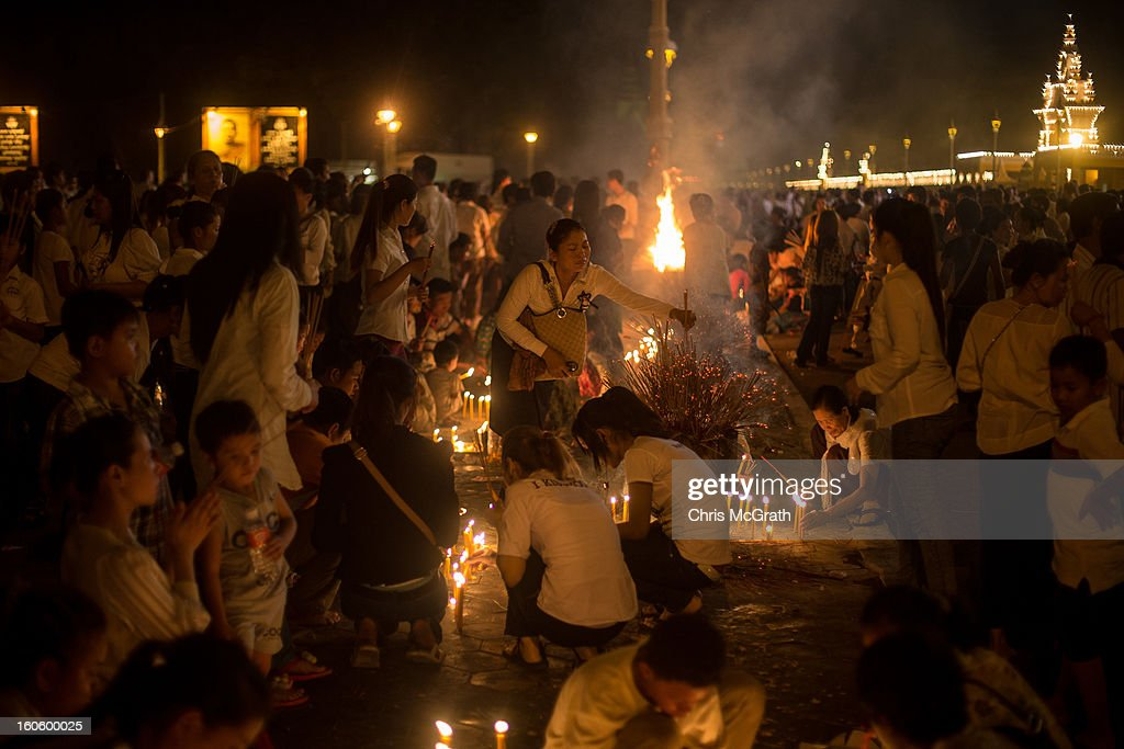 Hundreds of mourners pray and light incense in front of the Royal Palace on the eve of the cremation of former King Norodom Sihanouk on February 3, 2013 in Phnom Penh, Cambodia. The former kings coffin was transported to the cremation site after being paraded through the capital in a lavish funeral procession. The cremation will take place on Monday the 4th of February, the funeral pyre will be lit by his wife and son King Norodom Sihamoni.