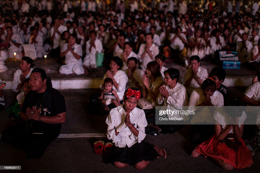 Hundreds of mourners pray in front of the Royal Palace on the eve of the cremation of former King Norodom Sihanouk on February 3, 2013 in Phnom Penh, Cambodia. The former kings coffin was transported to the cremation site after being paraded through the capital in a lavish funeral procession. The cremation will take place on Monday the 4th of February, the funeral pyre will be lit by his wife and son King Norodom Sihamoni.