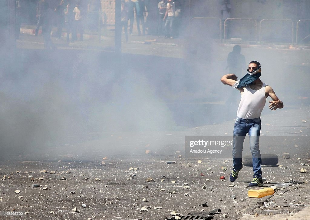 Hundreds of Palestinians throw stones to Palestinians security forces as they intervening the demonstration staged after Friday Prayer for Hamas, with tear gas in Hebron, West Bank on August 22, 2014.