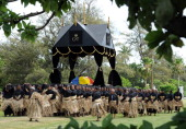 Hundreds of pall bearers all wearing black clothes and traditional woven ta'ovala mats around their waists carry the royal standard draped casket of...