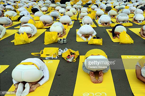 Hundreds of people attend a yoga session on the square at the foot of the Eiffel Tower on June 21 2015 in Paris France 192 countries join in for a...