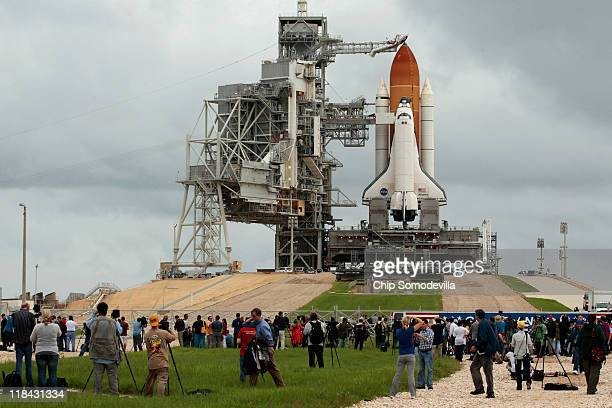 Hundreds of people gather near launch pad 39A to photograph and be photographed with the space shuttle Atlantis one day before its scheduled launch...