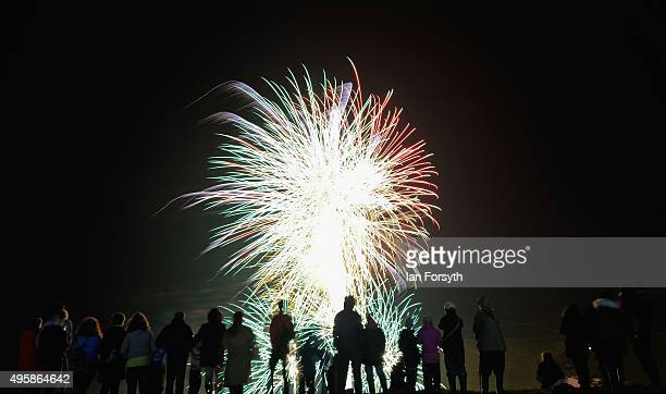 Hundreds of people stand on nearby cliffs as fireworks explode in the night sky as they attend the annual bonfire and fireworks display on November 5...