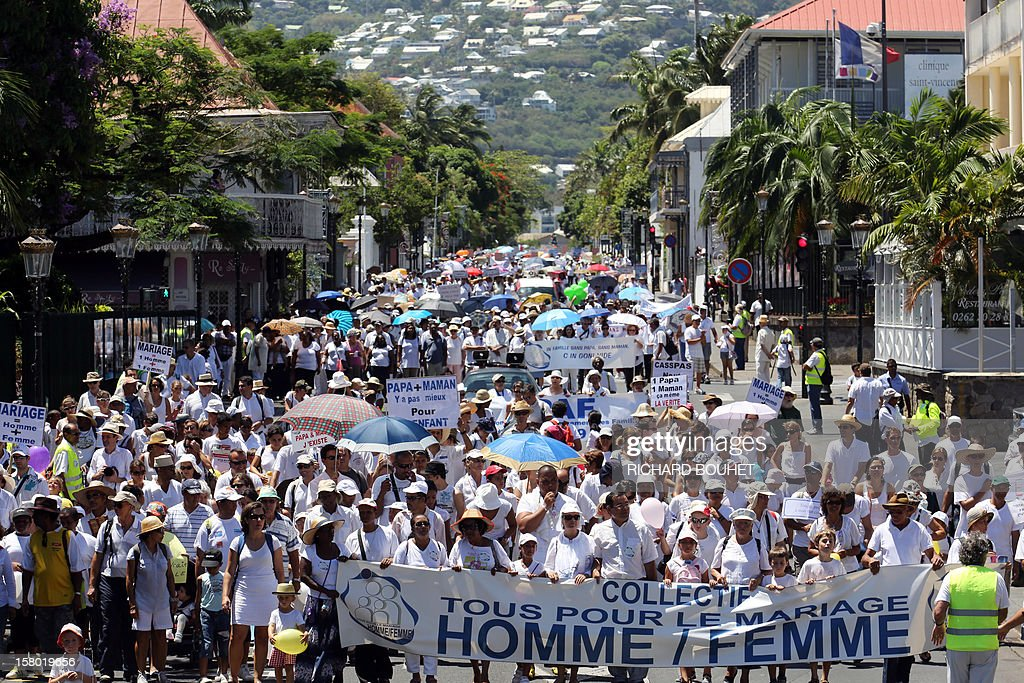 Hundreds of people which support the same-sex marriage demonstrate, on December 9, 2012, in Saint-Denis de la Reunion, on the French Indian Ocean island of La Reunion. France's Socialist government adopted on November 7, 2012 a draft law to authorise gay marriage and adoption despite fierce opposition from the Roman Catholic Church and the right-wing opposition. The front banner reads : 'Every one for the same-sex marriage', the name of the group of associations which organised the event. AFP PHOTO RICHARD BOUHET